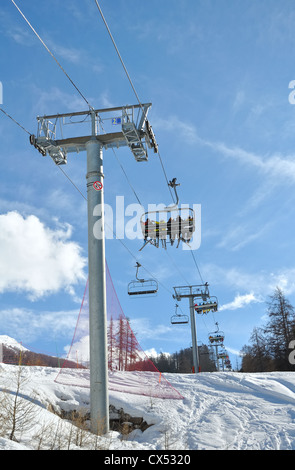 chairlifts carrying skiers to the slopes - Stock Photo