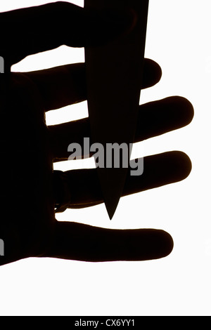 Violent scene with dagger pressed against fingers of a mans hand - Stock Photo