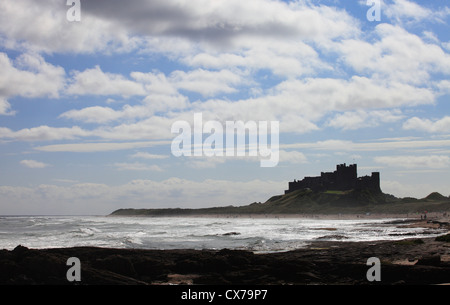 Bamburgh Castle, Northumberland, with waves and people enjoying a Summers day on the beach. - Stock Photo
