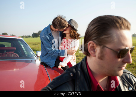 A rockabilly couple kissing while leaning on a vintage car, man in foreground - Stock Photo