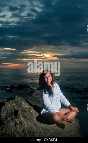 young girl sitting on the rocks by the beach bali, Indonesia. - Stock Photo