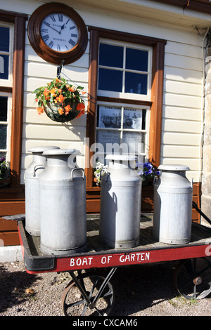 Milk churns on a cart at the restored Boat of Garten Steam Railway station in the Scottish Highlands - Stock Photo