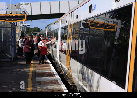 A stationery train at a station with people waiting to board - Stock Photo