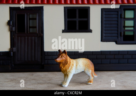 Concept photo: A toy guard dog guarding a house. - Stock Photo