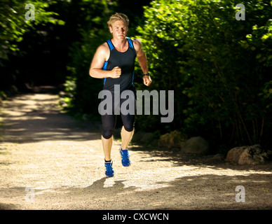 Fast athlete running in the forest - Stock Photo