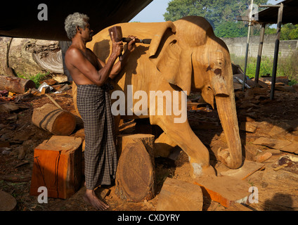 Sri Lankan wood carver making wooden statue of asian elephant, The Factory, Polonnaruwa, Sri Lanka, Asia - Stock Photo