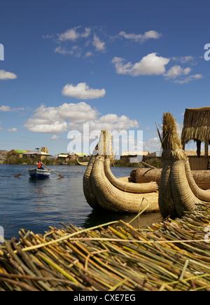 Aymara girl in a rowboat, Uros Island, Lake Titicaca, peru, South America - Stock Photo