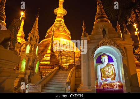 A BUDDHA STATUE and the main ZEDI of the SHWEDAGON PAGODA which dates from 1485 is gilded every year - YANGON, MYANAMAR - Stock Photo