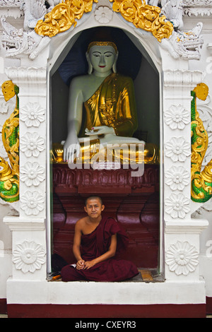 A young MONK sits below a BUDDHA STATUE at the SHWEDAGON PAYA or PAGODA which dates from 1485 - YANGON, MYANAMAR - Stock Photo