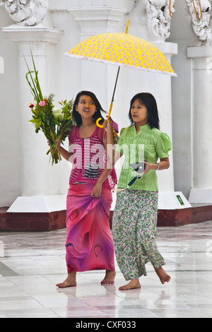 BURMESE GIRLS with umbrellas at the SHWEDAGON PAYA or PAGODA which dates from 1485 - YANGON, MYANAMAR - Stock Photo