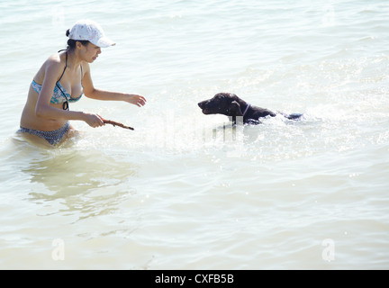 Happy lady on vacation swimming and playing with her dog. Artistic colors added - Stock Photo