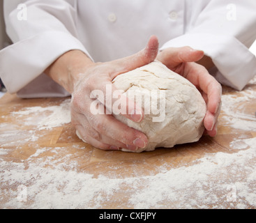 A woman's hands kneading dough on a cutting board - Stock Photo