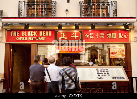 People outside a chinese restaurant in Gerrard Street, Chinatown London UK - Stock Photo