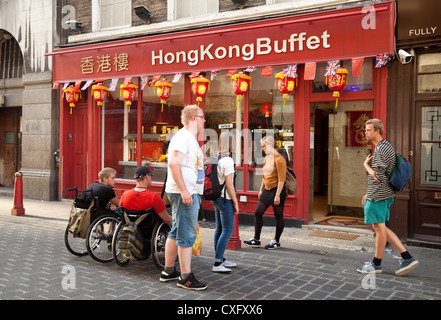 People outside a chinese restaurant, Gerrard St, Chinatown , London UK - Stock Photo