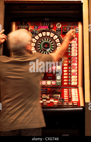 A man approximately 60 years old, (showing slight movement) placing a coin in a slot machine - Stock Photo