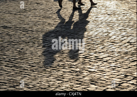 Europe, Italy, Rome, Two people walking on cobblestone pavement - Stock Photo