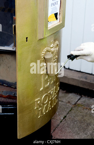 Painting postbox gold - Stock Photo