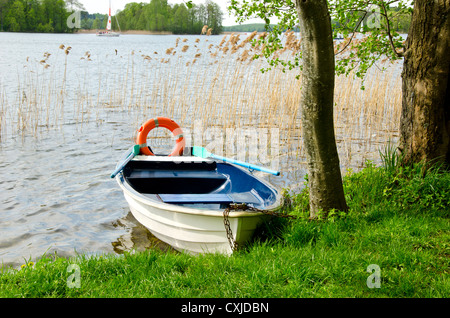 one boat on spring resort lake with life buoy - Stock Photo