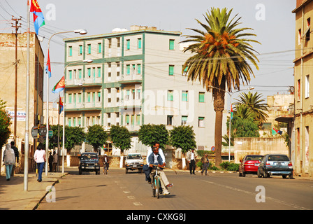 Eritrea, Asmara, men on a bicycle on the street with buildings in the background, people walking on the pathway - Stock Photo