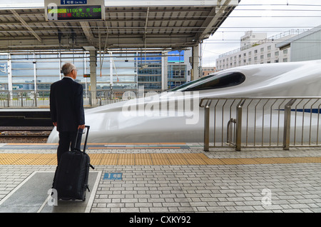 A passenger waits on a station platform as a bullet train arrives. - Stock Photo