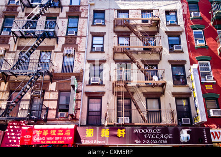 New York City - Aug 29:  Old tenement apartment buildings and businesses in New York City, Chinatown on August 29, - Stock Photo