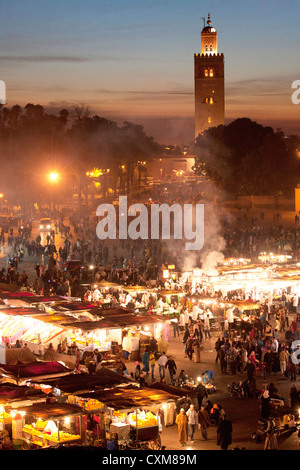 Market stalls and people at dusk in Fna Jamaa el Fna Square with Souk Koutoubia Minaret Mosque - Stock Photo