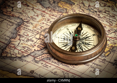 Old vintage retro brass compass on ancient map - Stock Photo