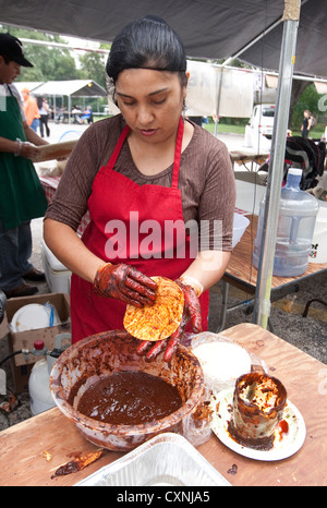 Hispanic woman prepares traditional Mexican enchiladas by covering corn tortilla with red chile sauce at outdoor - Stock Photo