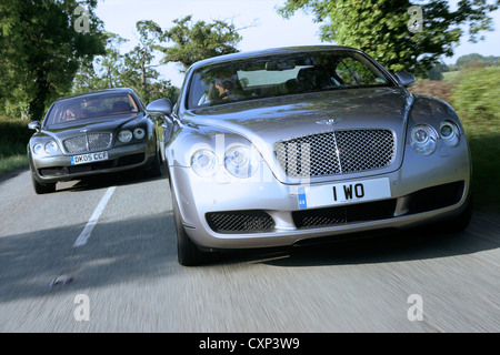 Bentley Continental Flying Spur and GT driving close on road - Stock Photo
