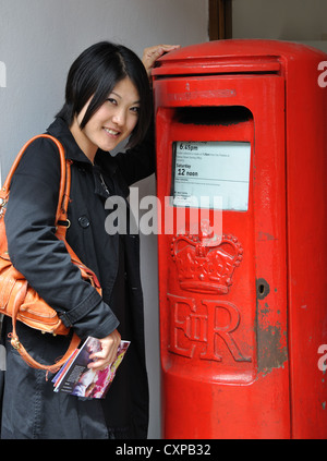 Young Japanese woman posting letters in traditional red Royal Mail letterbox, Stratford upon Avon, Warwickshire, - Stock Photo