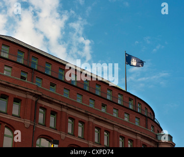 Flag of Free and Hanseatic City of Hamburg (Freie und Hansestadt Hamburg), flying and wavering high on the building. - Stock Photo