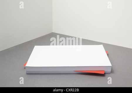 Red piece of paper amongst stack of blank paper - Stock Photo