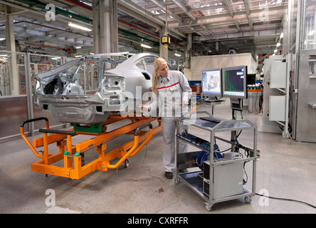 An Audi employee checking welding spots set by robots on a car body with a sensor, Audi plant in , Bavaria - Stock Photo