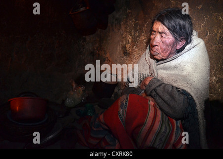 Indian woman, 80 years, sitting in her hut, Andes, border area of Bolivia and Peru, South America - Stock Photo