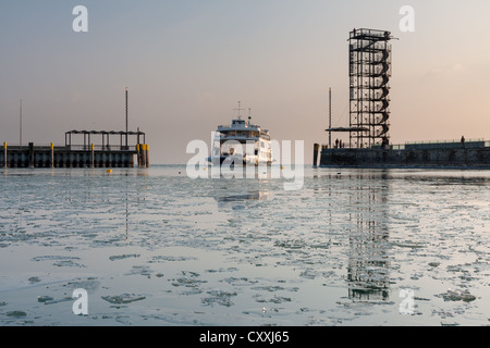 Port basin with entering ferry and ice floes in the evening light, Friedrichshafen on Lake Constance, Bodenseekreis - Stock Photo