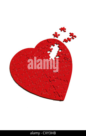 Red heart-shaped jigsaw puzzle, incomplete - Stock Photo