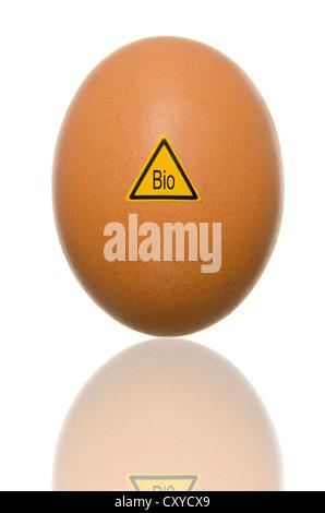 Single egg with warning sign 'Bio', symbolic image, caution: organic eggs - Stock Photo