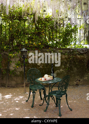Still life, cheese buffet on an round, antique cast-iron garden table with two chairs in a romantic courtyard - Stock Photo