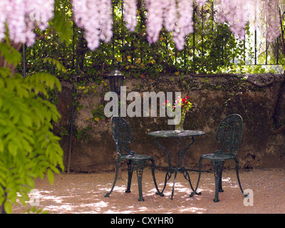 Still life, round, antique cast-iron garden table and two chairs, in a romantic courtyard - Stock Photo