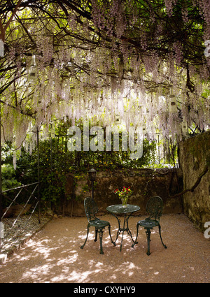 Round, cast-iron garden bistro table with two chairs in a romantic backyard - Stock Photo