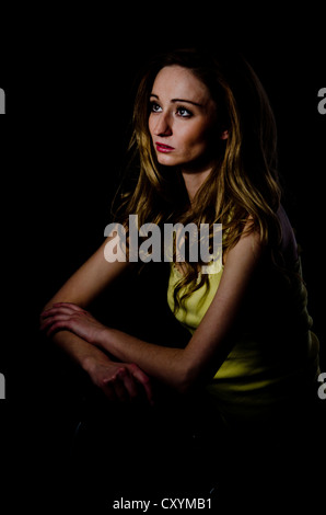 Young woman, 25, sitting in a dark environment - Stock Photo