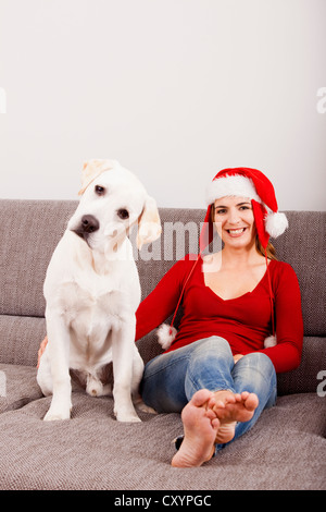 Woman sitting on the sofa with her dog and wearing a Santa hat - Stock Photo