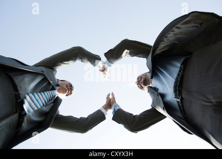 Business team joining hands to celebrate their success - Stock Photo