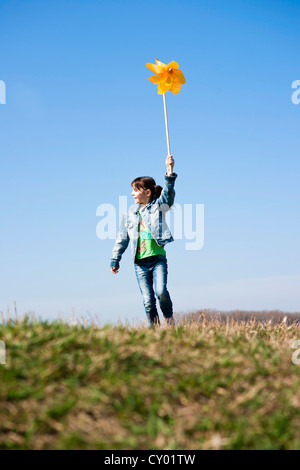 Girl holding up a pinwheel in a field - Stock Photo