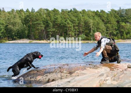 The Labrador retriever fetch a dummy for its owner - Stock Photo