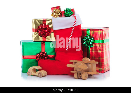 Photo of a red Christmas stocking with gift wrapped presents and toys, isolated on a white background. - Stock Photo