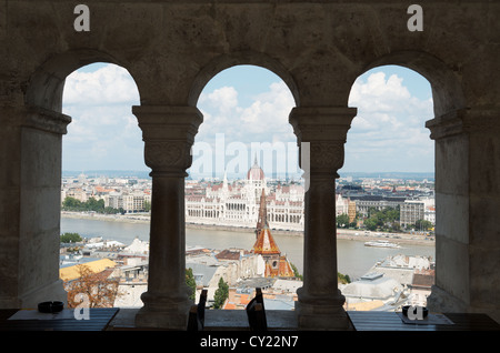 Hungarian Parliament building seen through the arches of Fisherman's Bastion on Castle Hill in Budapest, Hungary - Stock Photo