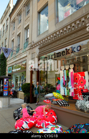 Boston Massachusetts Back Bay Newbury Street high-end luxury name-brand shopping girl playing bean bag chair Marimekko - Stock Photo