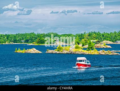 Small boat on lake near island in Georgian Bay, Ontario Canada - Stock Photo
