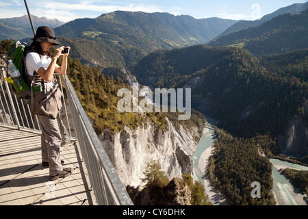 A woman tourist taking a photo from Il Spir looking down at the River Rhine in the gorge at Conn, Flims, Switzerland - Stock Photo